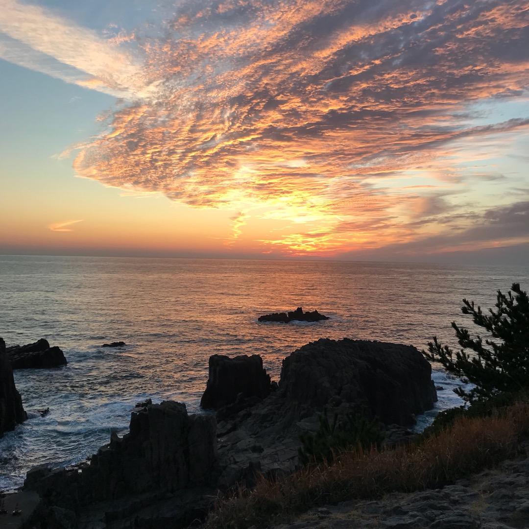 東尋坊。夕暮れ時。 夕暮れ時には人々が岸壁の上に腰を下ろして日が落...