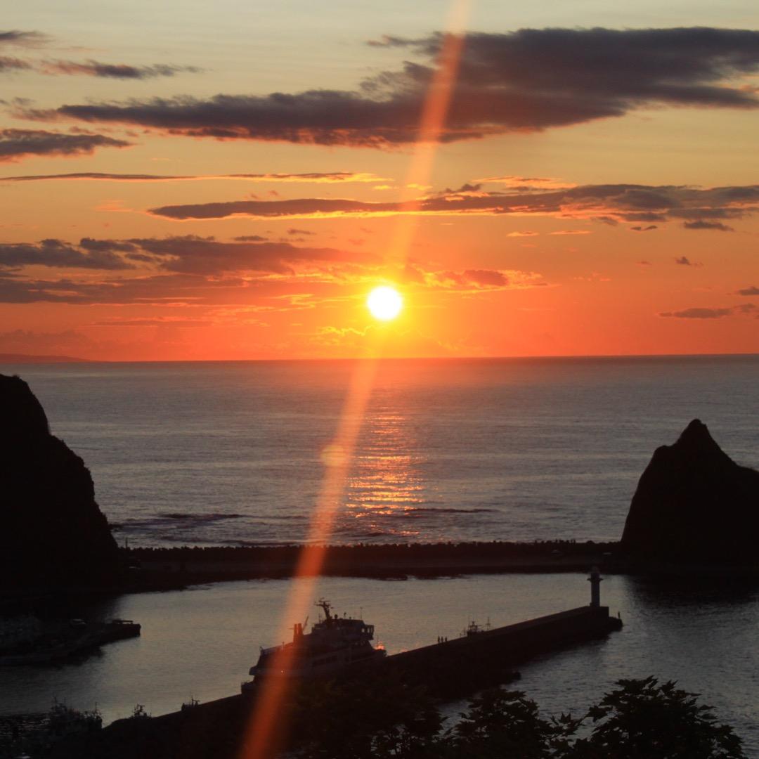 北海道世界遺産の知床半島ウロト港に沈む夕日はオホーツク海に金色の道...